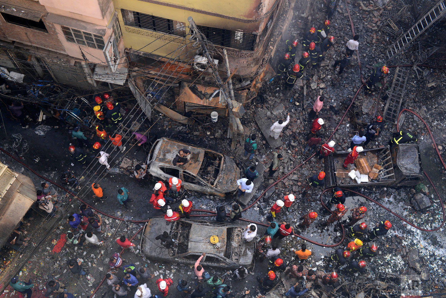 Rescuers stand at the site of a late Wednesday night fire in Dhaka, Bangladesh, Thursday, Feb. 21, 2019. (AP Photo/Mahmud Hossain Opu)