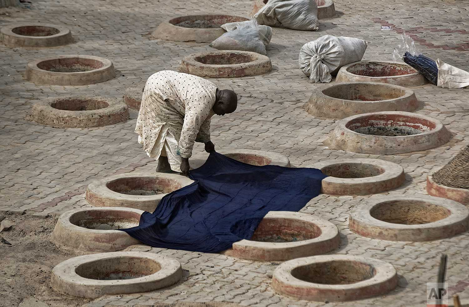 In this photo taken Tuesday, Feb. 19, 2019, a craftsman lays indigo-dyed cloth to dry over some of the ancient dye pits of Kofar Mata in Kano, northern Nigeria. (AP Photo/Ben Curtis)