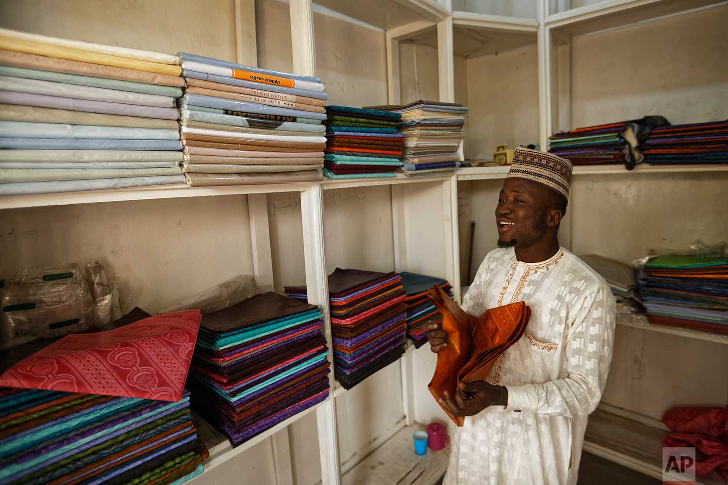 In this photo taken Tuesday, Feb. 19, 2019, a shopkeeper sells dyed fabric made in China at his stall in the market in Kano, northern Nigeria. (AP Photo/Ben Curtis)