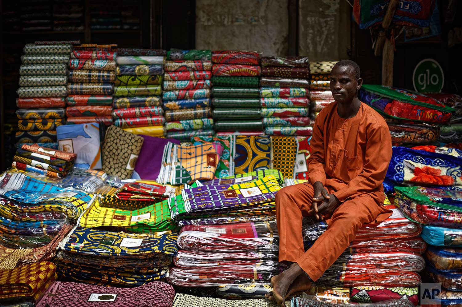 In this photo taken Tuesday, Feb. 19, 2019, a shopkeeper sits at his stall selling a variety of wax-printed fabrics made in China that fill the market in Kano, northern Nigeria. (AP Photo/Ben Curtis)