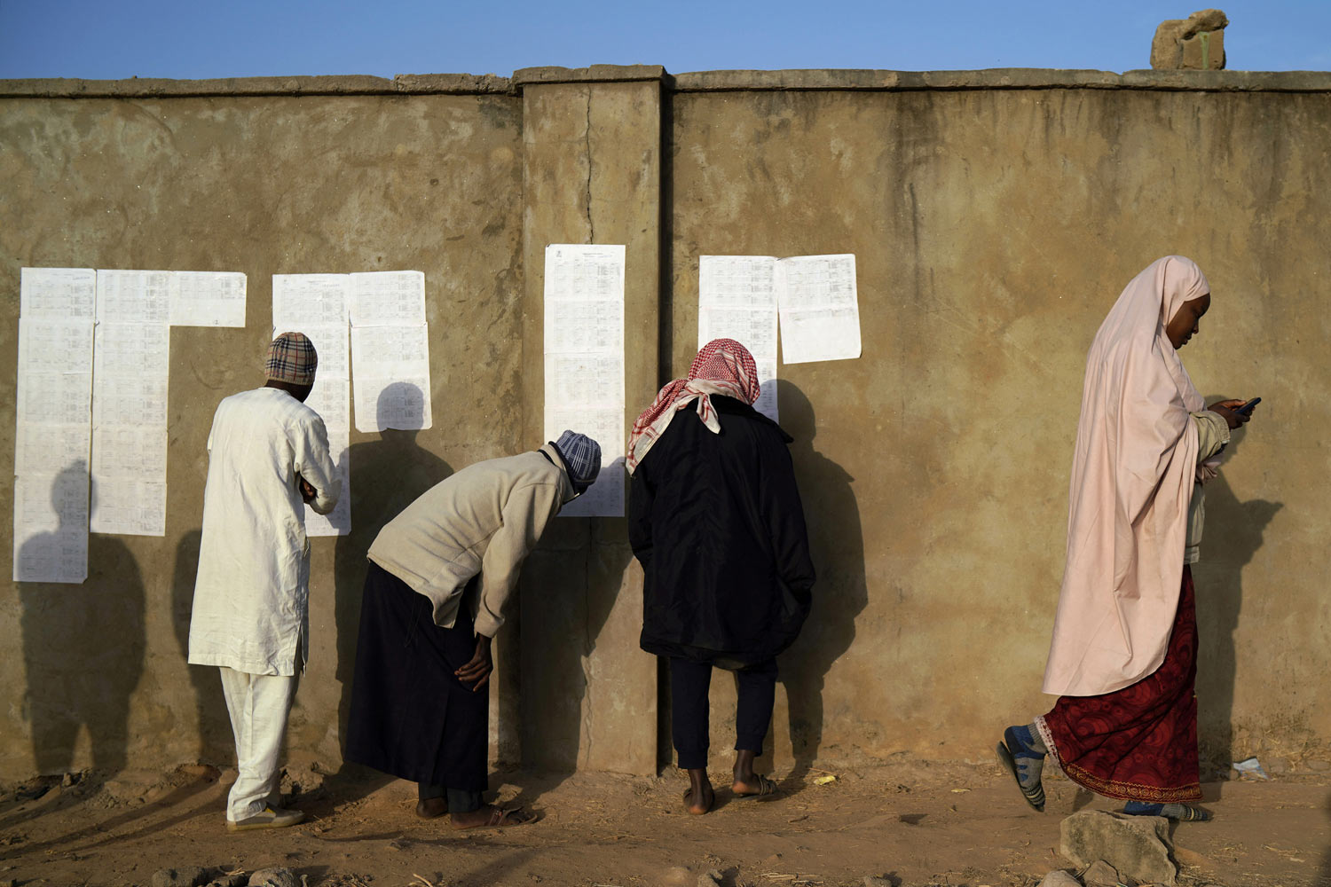 People check voters lists at a polling station in Kaduna, Nigeria, Saturday, Feb. 16, 2019. Nigeria's electoral commission delayed the presidential election until Feb. 23, making the announcement only five hours before polls were set to open. President Muhammadu Buhari is in a tight race with a former vice president, Atiku Abubakar. Both have signed pledges to contribute to a peaceful election but their supporters have kept up a wave of heated rhetoric. (AP Photo/Jerome Delay)