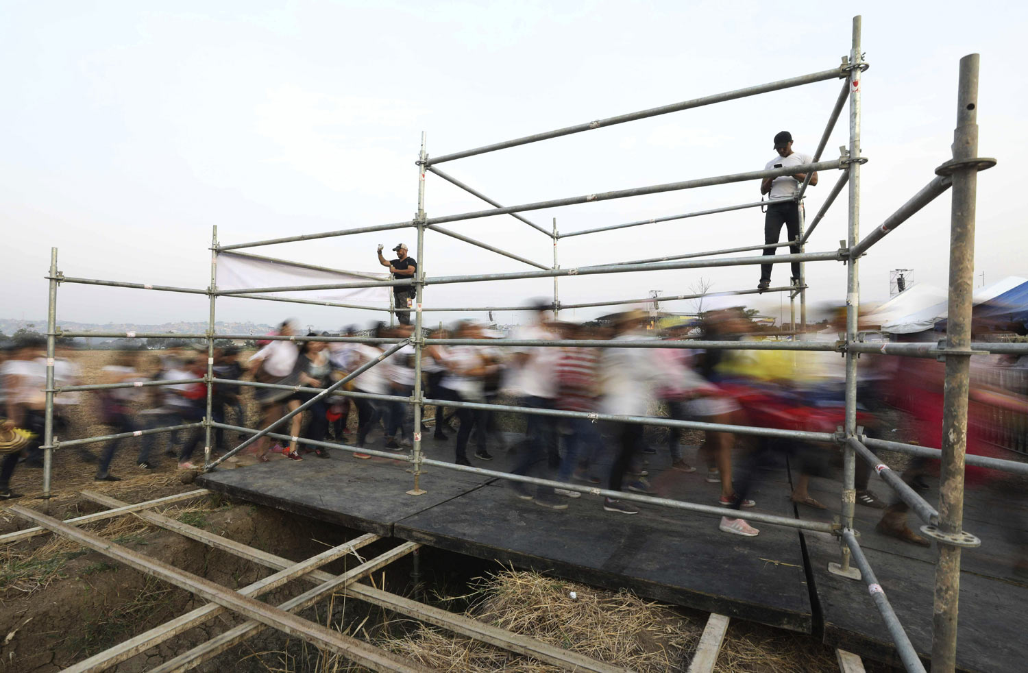 People stream through a gate before the Venezuela Aid Live concert on the Colombian side of Tienditas International Bridge on the outskirts of Cucuta, Colombia, on the border with Venezuela, Friday, Feb. 22, 2019. Venezuela's power struggle is set to convert into a battle of the bands Friday when musicians demanding Nicolas Maduro allow in humanitarian aid and those supporting the embattled leader's refusal sing in rival concerts being held at both sides of a border bridge where tons of donated food and medicine are being stored. (AP Photo/Fernando Vergara)
