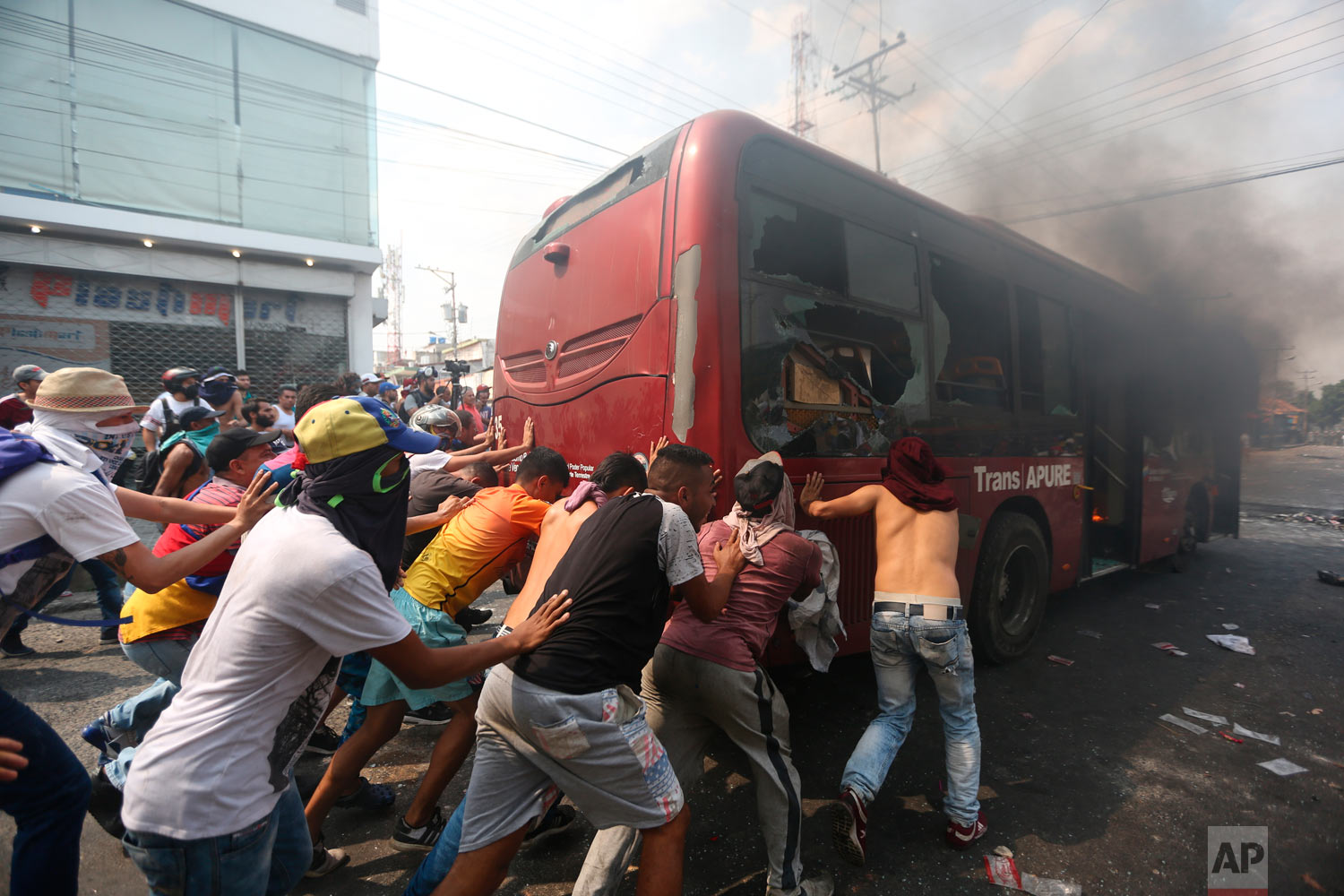 Demonstrators push away a bus that was torched during clashes with the Venezuelan Bolivarian National Guard in Urena, Venezuela, near the border with Colombia, Saturday, Feb. 23, 2019. (AP Photo/Fernando Llano)
