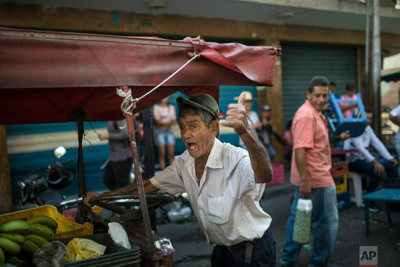 A street vendor chants anti-government slogans in San Antonio del Tachira, Venezuela, near the border with Colombia, Friday, Feb. 22, 2019. (AP Photo/Rodrigo Abd)