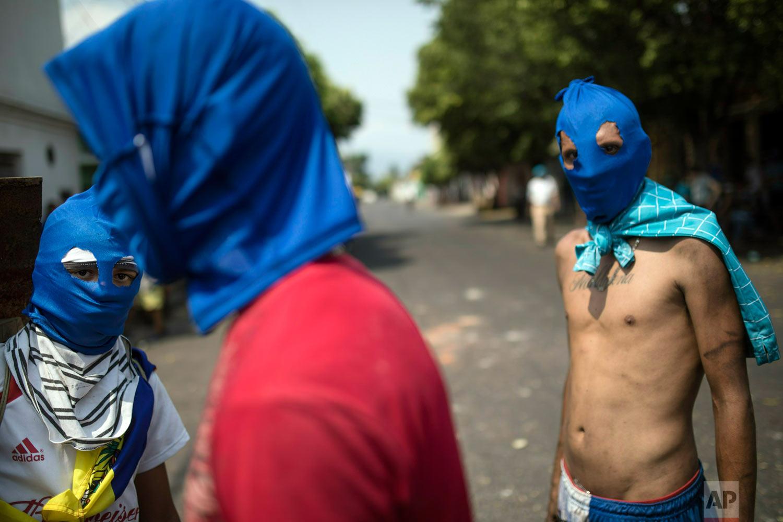 Masked anti-government protesters gather a few blocks from the border bridge in Urena, Venezuela, Sunday, Feb. 24, 2019, where Venezuelan soldiers continue to block humanitarian aid from entering. (AP Photo/Rodrigo Abd)