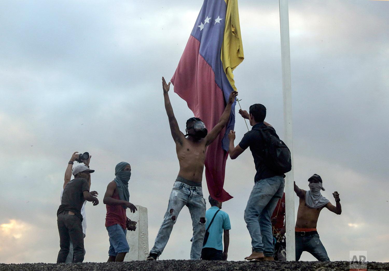 Protestors bring down the Venezuelan national flag at the border between Brazil and Venezuela, in Pacaraima, Roraima state, Brazil, Saturday, Feb. 23, 2019. (AP Photo/Ivan Valencia)