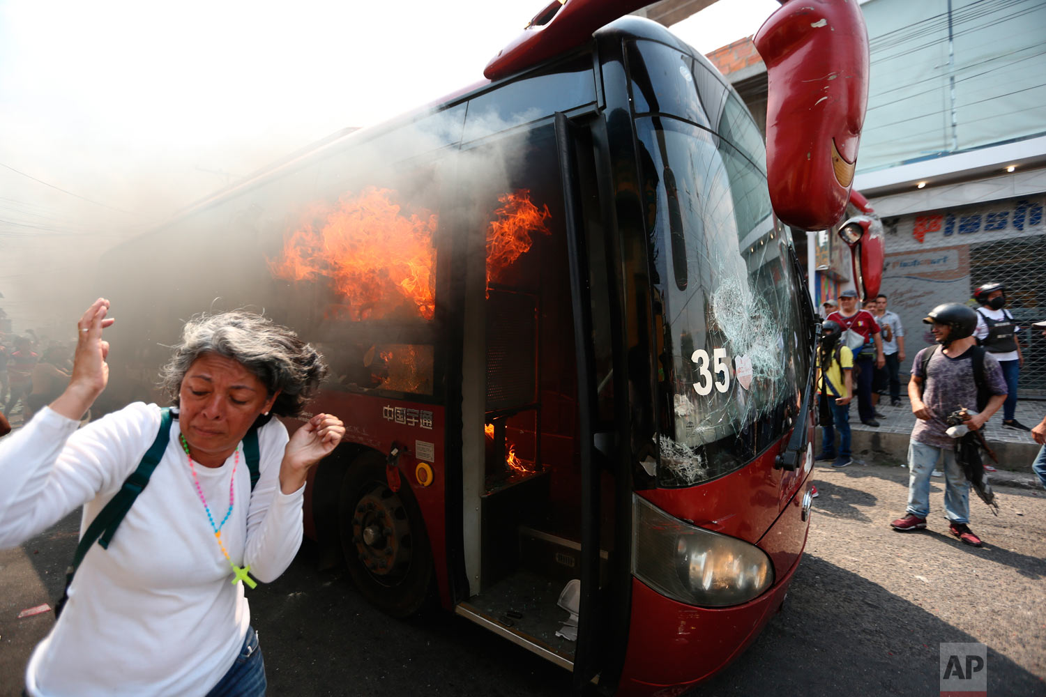 A woman moves away from the flames of a burning bus after it was pushed away during clashes with the Venezuelan Bolivarian National Guard in Urena, Venezuela, near the border with Colombia, Saturday, Feb. 23, 2019. (AP Photo/Fernando Llano)