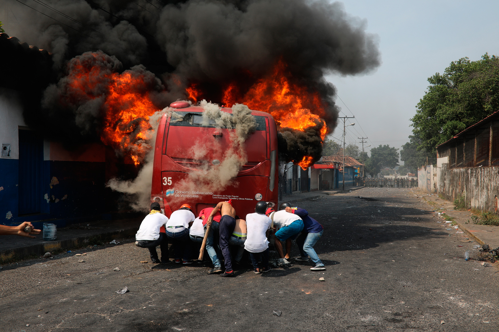 Demonstrators push a bus that was torched during clashes with the Venezuelan Bolivarian National Guard in Urena, Venezuela, near the border with Colombia, Saturday, Feb. 23, 2019. (AP Photo/Rodrigo Abd)