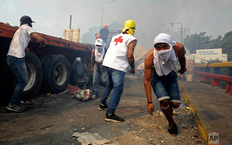 Venezuelan youth clash with  Venezuelan National Guard next to a semi-trailer that was part of a humanitarian aid convoy that failed to cross the Francisco de Paula Santander international bridge in Cucuta, Colombia, Saturday, Feb. 23, 2019. (AP Photo/Fernando Vergara)