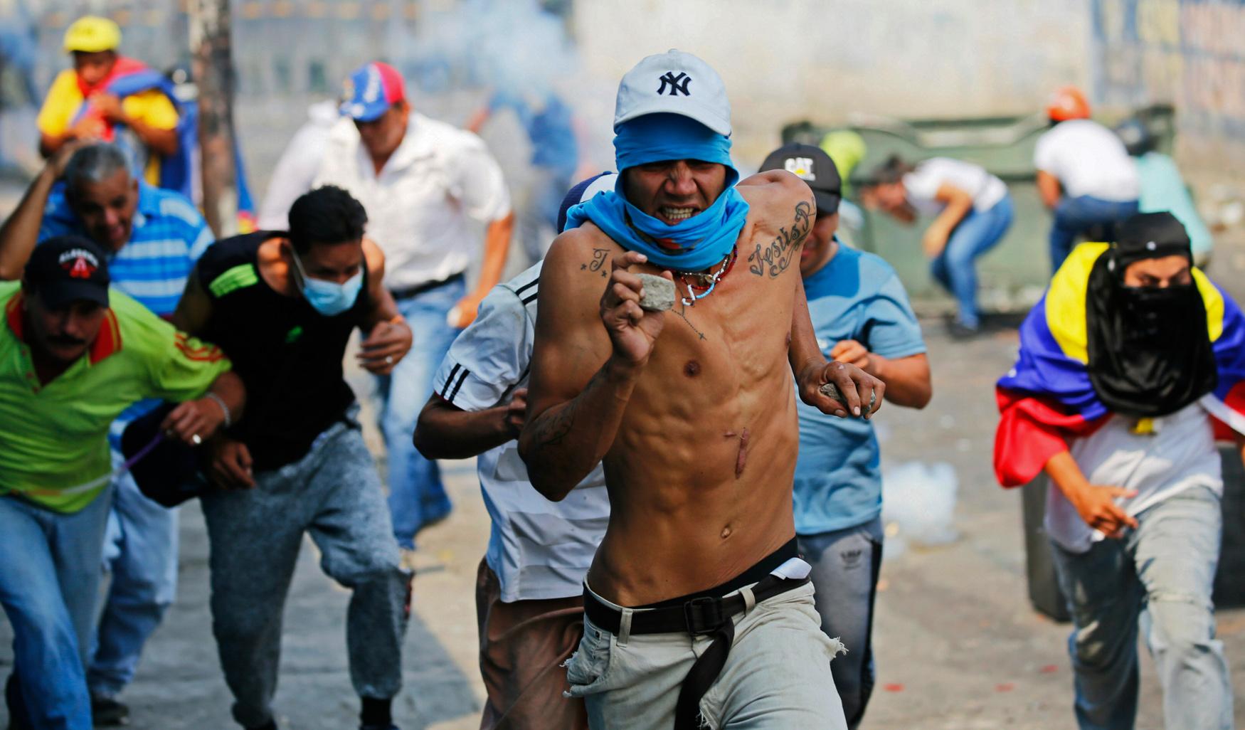 Demonstrators run from tear gas fired by Venezuelan Bolivarian National Guards in Urena, Venezuela, near the border with Colombia, Saturday, Feb. 23, 2019.  (AP Photo/Fernando Llano)