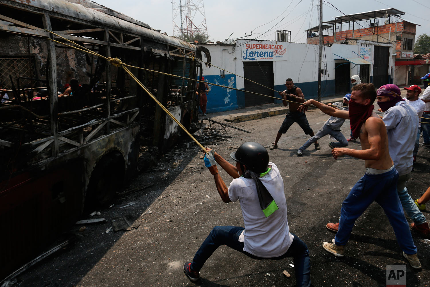 Demonstrators move a torched bus during clashes with the Venezuelan Bolivarian National Guard in Urena, Venezuela, near the border with Colombia, Saturday, Feb. 23, 2019. (AP Photo/Rodrigo Abd)