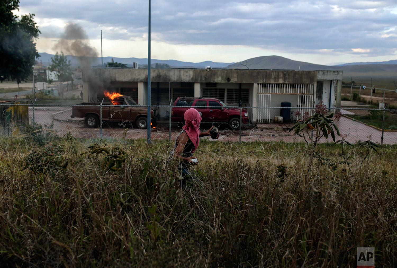 A demonstrator throws a stone at a Venezuelan military post at the border between Brazil and Venezuela, in Pacaraima, Roraima state, Brazil, Saturday, Feb.23, 2019. (AP Photo/Ivan Valencia)