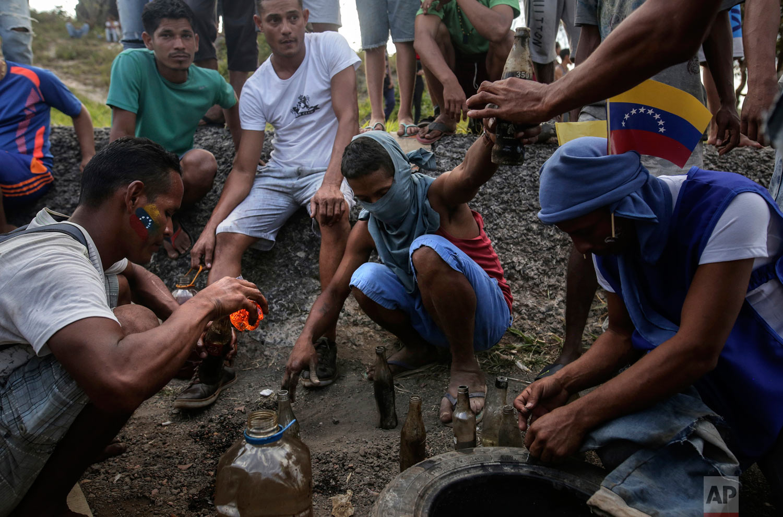 Demonstrators prepare gasoline bombs during a protest at the border between Brazil and Venezuela, in Pacaraima, Roraima state, Brazil, Saturday, Feb.23, 2019. (AP Photo/Ivan Valencia)