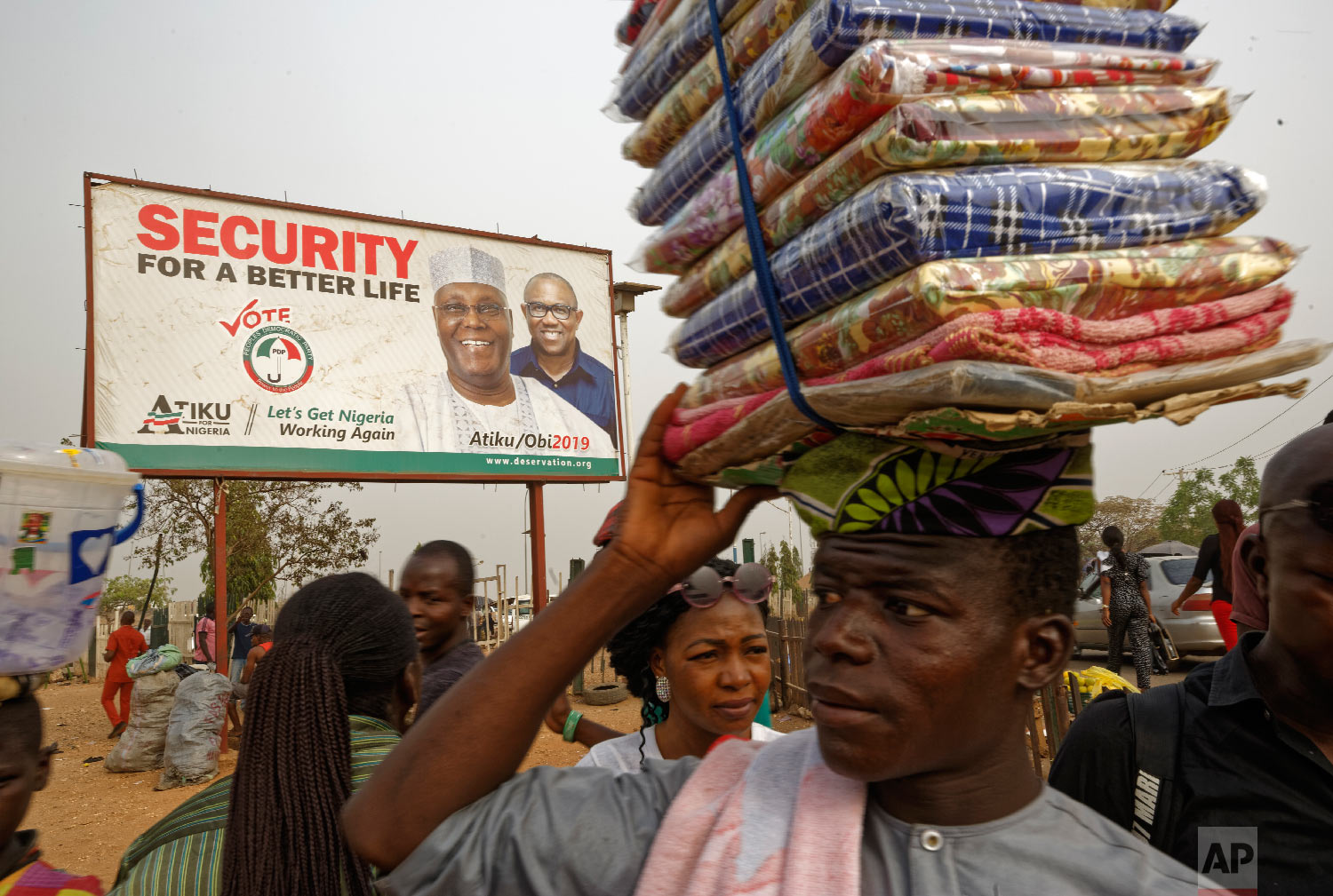A street seller sells his wares by the side of the road next to a campaign poster for opposition presidential candidate Atiku Abubakar, at a busy intersection near Nyanya, on the eastern outskirts of the capital Abuja, Nigeria, Feb. 12, 2019. (AP Photo/Ben Curtis)