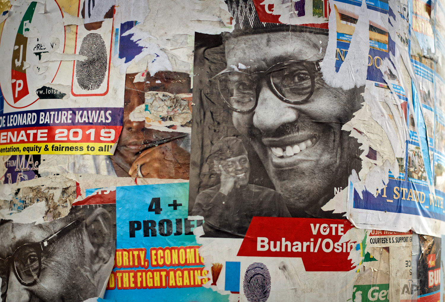 The faces of incumbent President Muhammadu Buhari and Vice President Yemi Osinbajo are seen on partially-ripped campaign posters near Nyanya, on the eastern outskirts of the capital Abuja, Nigeria, Feb. 12, 2019. (AP Photo/Ben Curtis)