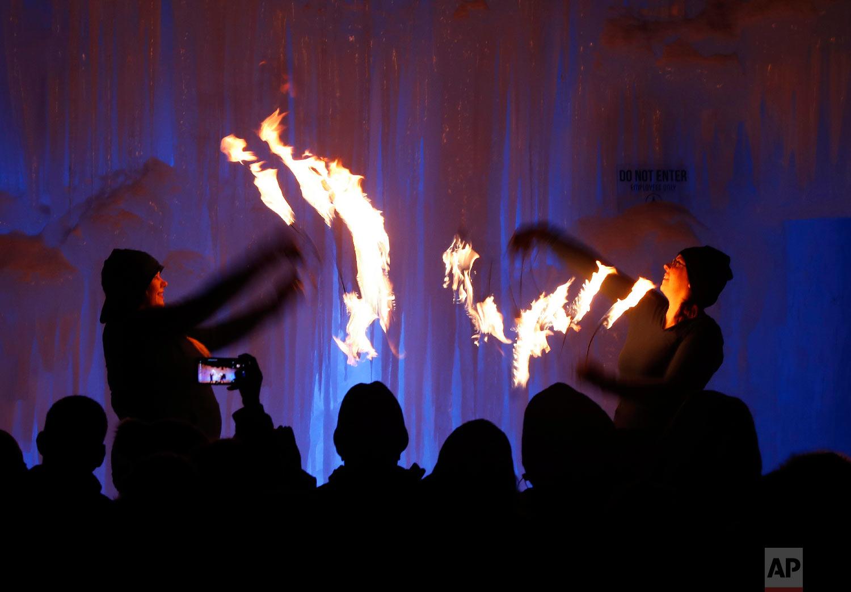 Fire dancers perform at Ice Castles, in North Woodstock, N.H., on Jan. 25, 2019. (AP Photo/Robert F. Bukaty)