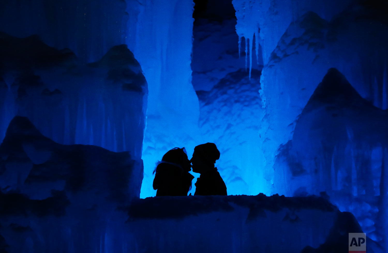 "Romance heats up for a couple at Ice Castles in North Woodstock, N.H., on Jan. 25, 2019. ""It's a really popular date night spot,"" said castle builder Matt Pasciuto. ""I can't tell you how many marriage proposals I've seen so far in the castle."" (AP Photo/Robert F. Bukaty)"