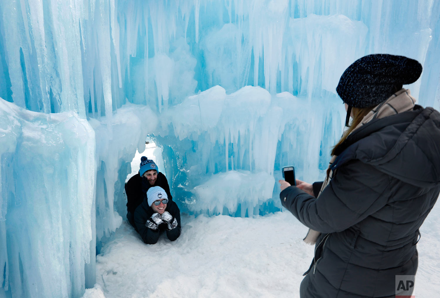 Visitors pose for a photo in a tunnel at Ice Castles Jan. 26, 2019, in North Woodstock, N.H. (AP Photo/Robert F. Bukaty)