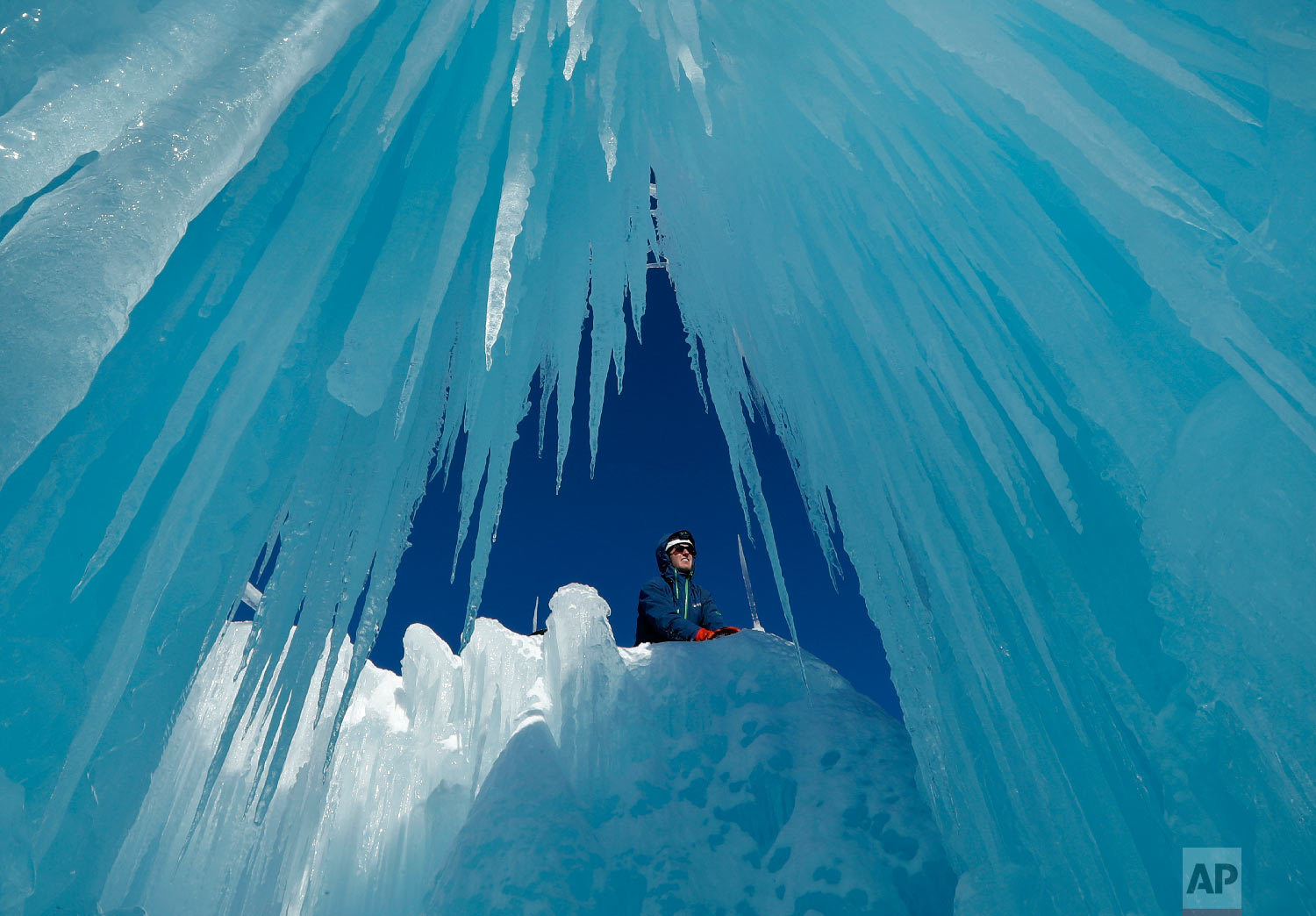 Matt Pasciuto places an icicle at the top of a wall at Ice castles in North Woodstock, N.H., on Jan. 28, 2019. (AP Photo/Robert F. Bukaty)