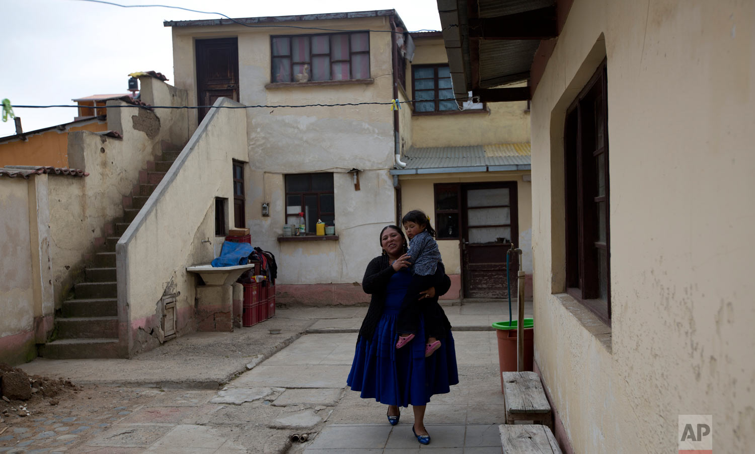 Reyna Torrez carries her daughter Lydia after an interview at her home in El Alto, Bolivia, Monday, Feb. 18, 2019. (AP Photo/Juan Karita)