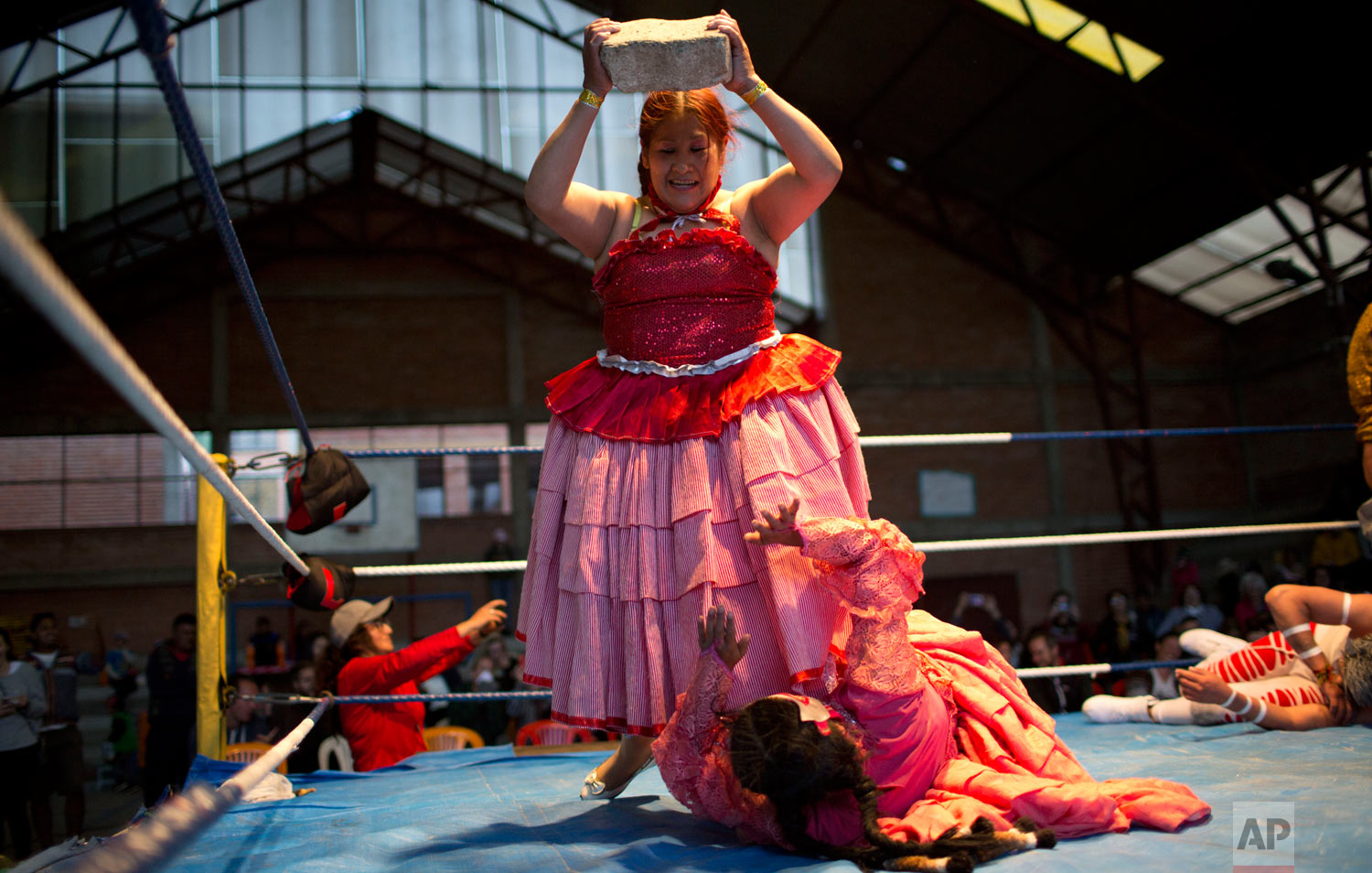 Veteran cholita wrestler Jennifer dos Caras, 45, holds a cement block over teen wrestler Lucero la Bonita in the ring in El Alto, Bolivia, Monday, Jan. 21, 2019. (AP Photo/Juan Karita)