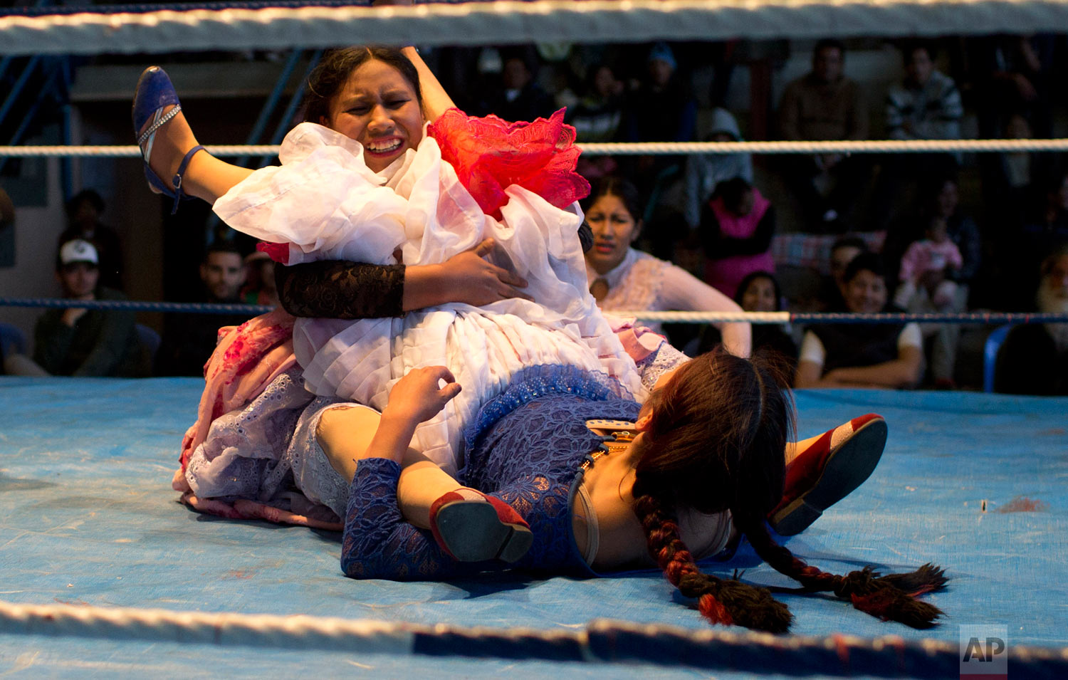 Young cholita wrestler Dona Chevas, 16, top, holds the legs of her rival, fellow trainee Simpatica Sonia, 24, as they compete in the ring in El Alto, Bolivia, Thursday, Jan. 21, 2019. (AP Photo/Juan Karita)