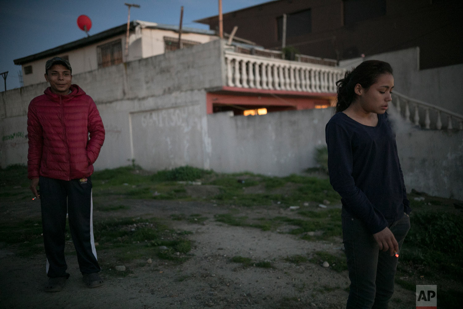 Seventeen-year-old Honduran migrant Josue Mejia Lucero, left, smokes along with his girlfriend's sister Xiomara Henriquez Ayala, 13, outside the Agape World Mission shelter in Tijuana, Mexico, Feb. 8, 2019. (AP Photo/Emilio Espejel)