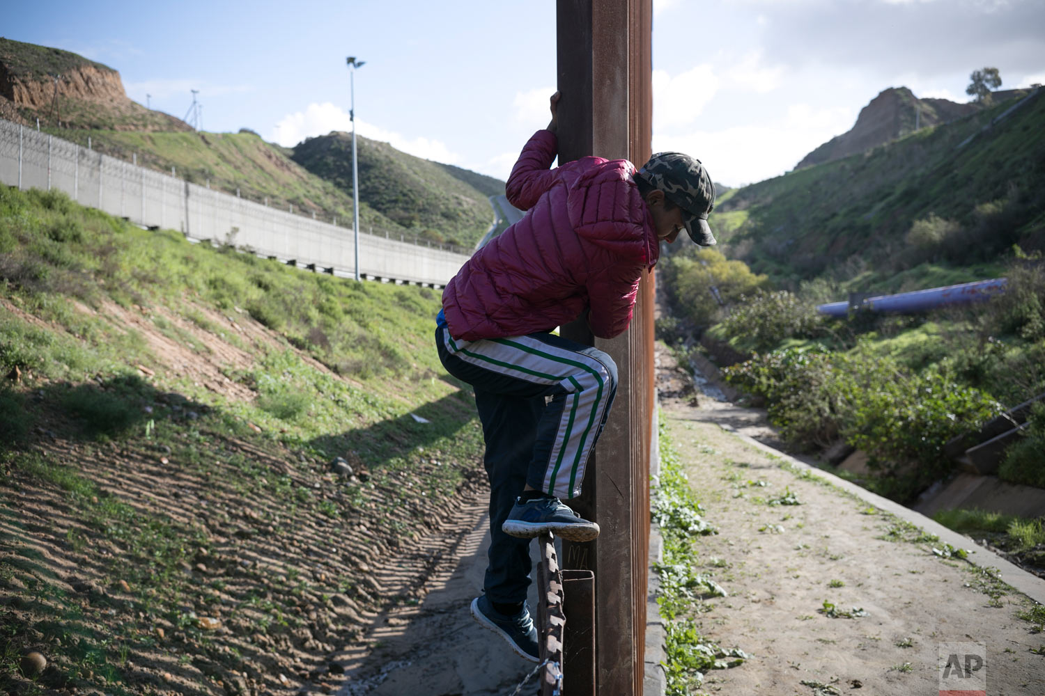 Teen Honduran migrant Josue Mejia Lucero climbs back over the U.S. border fence from San Diego to Tijuana, Mexico, after crossing it briefly to scout the area in an attempt to help his sister and her son reach the U.S. undetected from Tijuana, Mexico, Feb. 3, 2019. (AP Photo/Emilio Espejel)