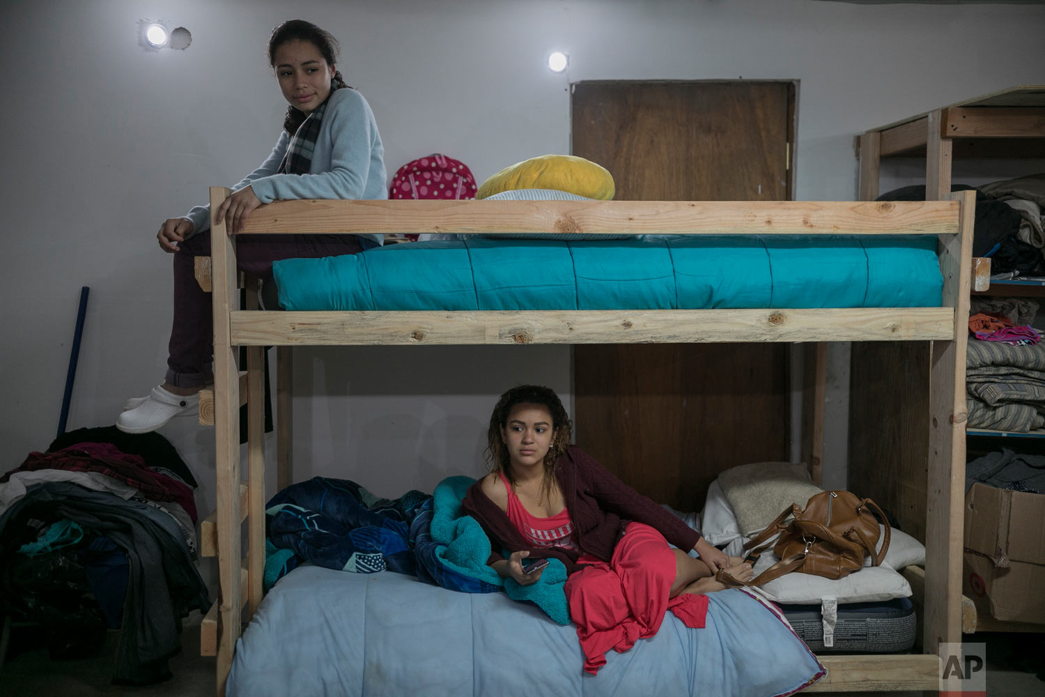 EL Salvador migrant Xiomara, 13, sits atop the bunk bed she shares with 18-year-old Valeria Ramos of Honduras, at the Agape World Mission shelter in Tijuana, Mexico, Feb. 4, 2019. (AP Photo/Emilio Espejel)