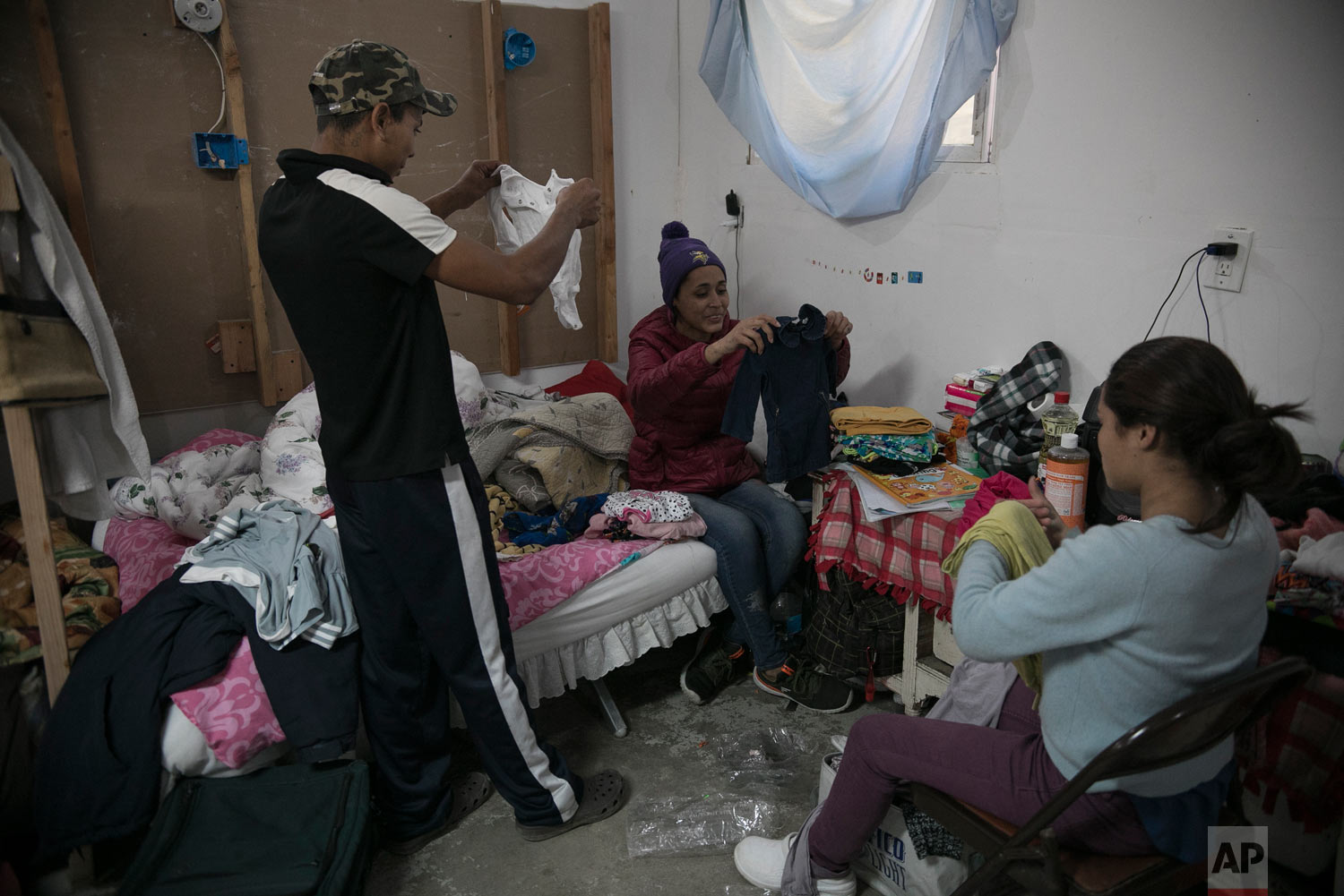 Central American migrants, 17-year-old Josue Mejia Lucero, left, 15-year-old Milagro de Jesus Henriquez Ayala, who is pregnant, center, and her younger sister Xiomara,13, organize baby clothes they selected from among donated items, in their room at the Agape World Mission shelter in Tijuana, Mexico, Feb. 6, 2019. (AP Photo/Emilio Espejel)