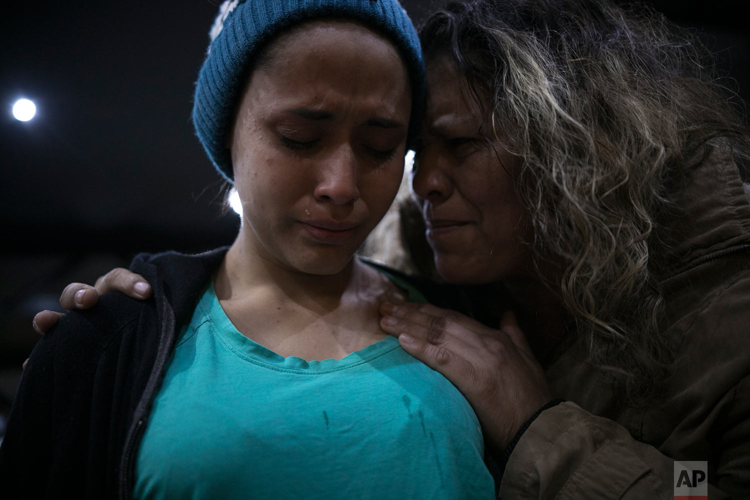 Pregnant 15-year-old El Salvador migrant Milagro de Jesus Henriquez Ayala, is comforted by a local church member as she cries during a Christian religious service at the Agape World Mission shelter in Tijuana, Mexico, Feb. 8, 2010. (AP Photo/Emilio Espejel)