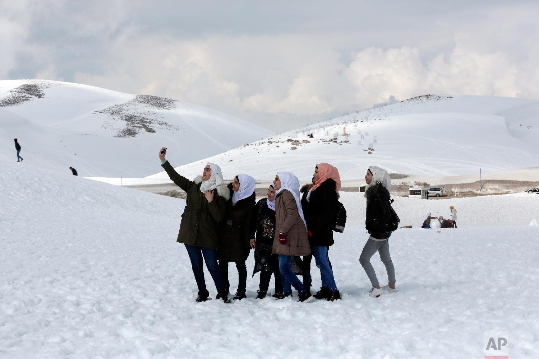Syrian girls take a selfie at the Faraya-Mzaar ski resort, in Faraya, northeast of Beirut, Lebanon, Feb. 22, 2019. (AP Photo/Bilal Hussein)