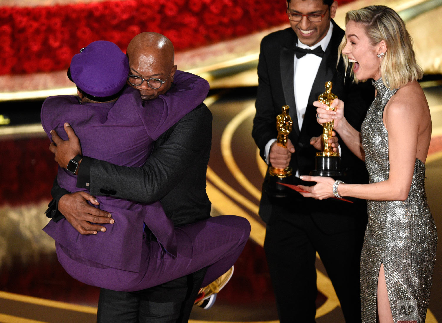"Samuel L. Jackson, center left, embraces Spike Lee, winner of the award for best adapted screenplay for ""BlacKkKlansman"" as Brie Larson, right, looks on, at the Oscars on Sunday, Feb. 24, 2019, at the Dolby Theatre in Los Angeles. (Photo by Chris Pizzello/Invision/AP)"
