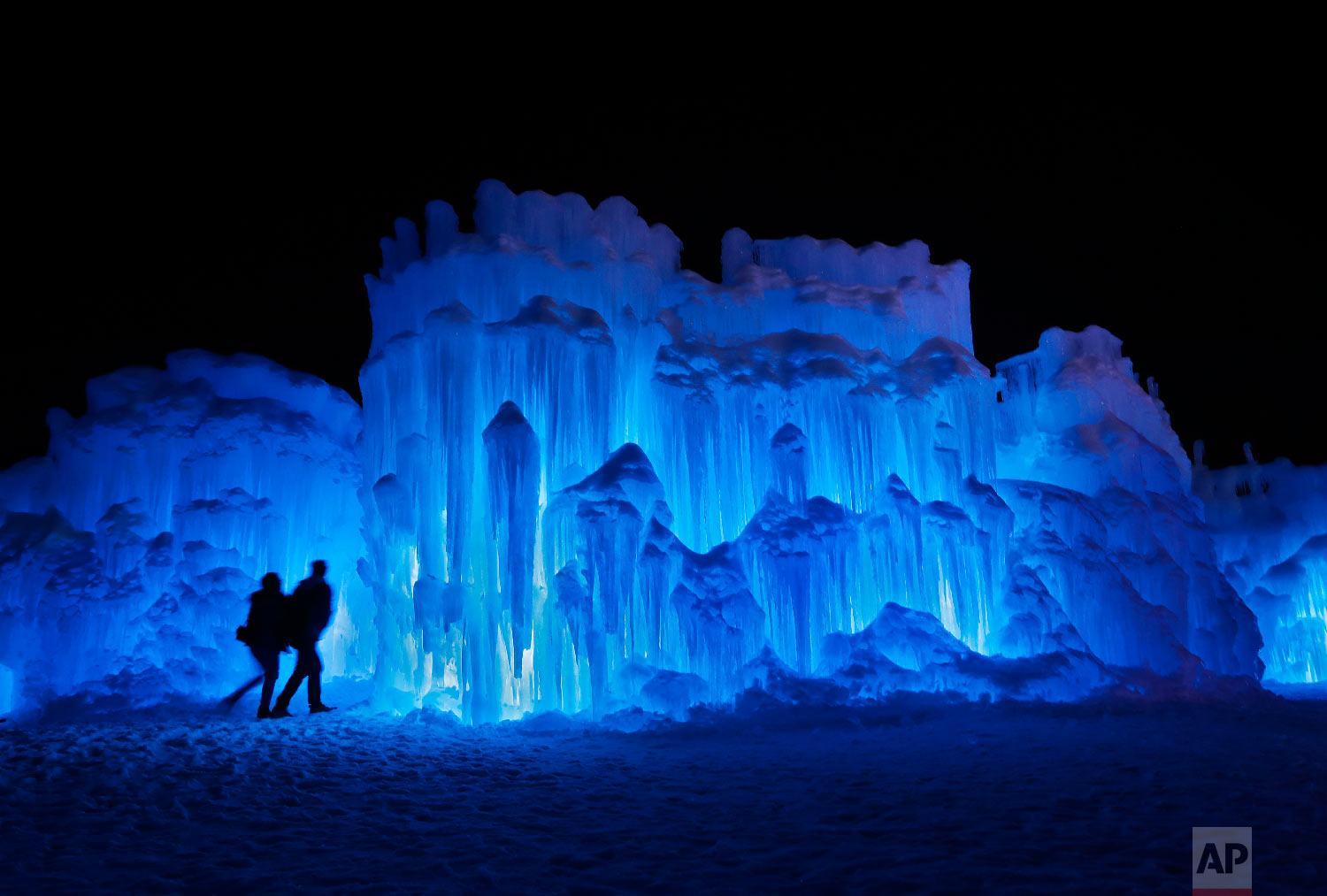 In this Saturday, Jan. 26, 2019, photo, a couple heads towards an entrance to a cavern at Ice Castles in North Woodstock, N.H.  (AP Photo/Robert F. Bukaty)