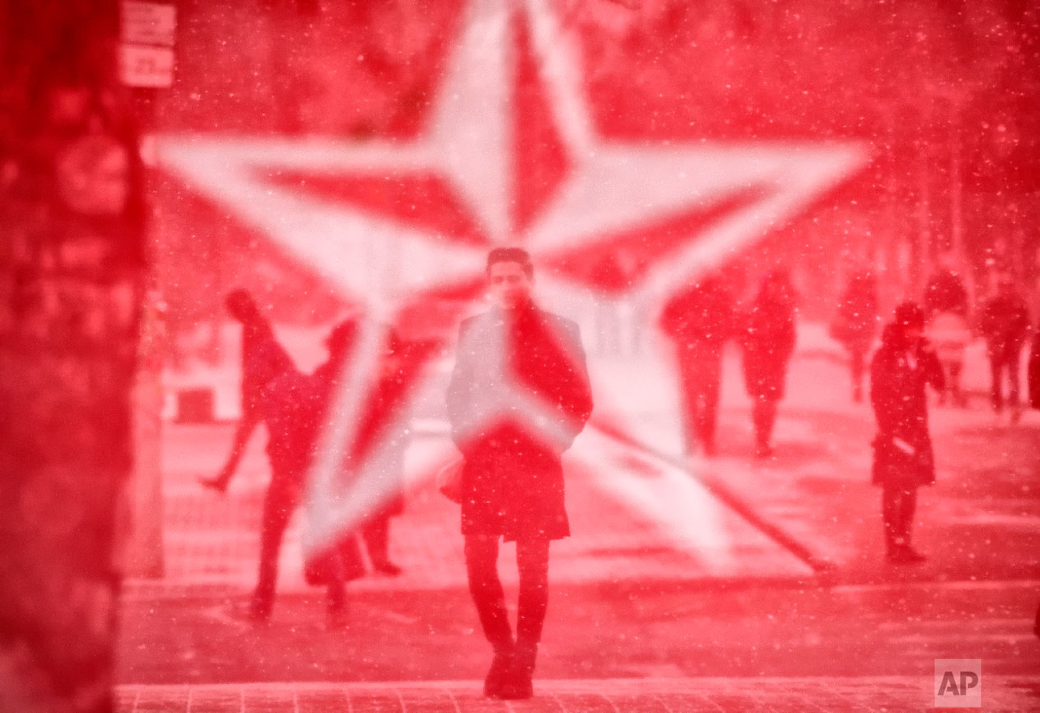 Seen through the mesh covering an electoral advertising point of the Socialits' Party, people walk in Chisinau, Moldova, Saturday, Feb. 23, 2019, a day before the country holds parliamentary elections.  (AP Photo/Vadim Ghirda)