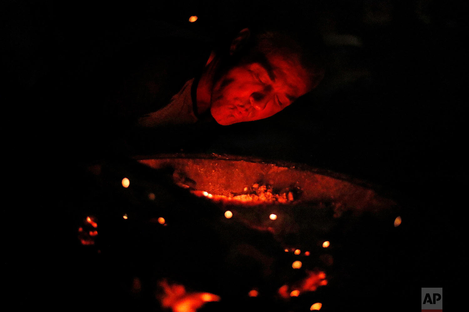 Gene Hogan blows on a campfire outside the tent he's living in since becoming homeless from Hurricane Michael in Youngstown, Fla, Wednesday, Jan. 23, 2019. (AP Photo/David Goldman)