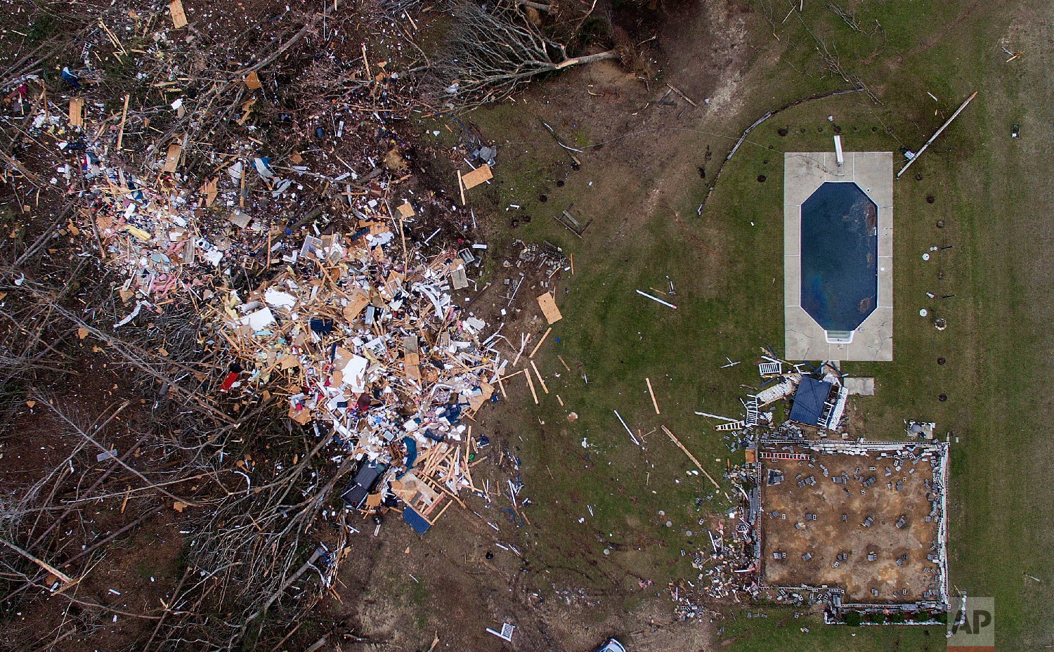 Debris from a home litters a yard the day after a tornado blew it off its foundation, lower right, in Beauregard, Ala., March 4, 2019. (AP Photo/David Goldman)