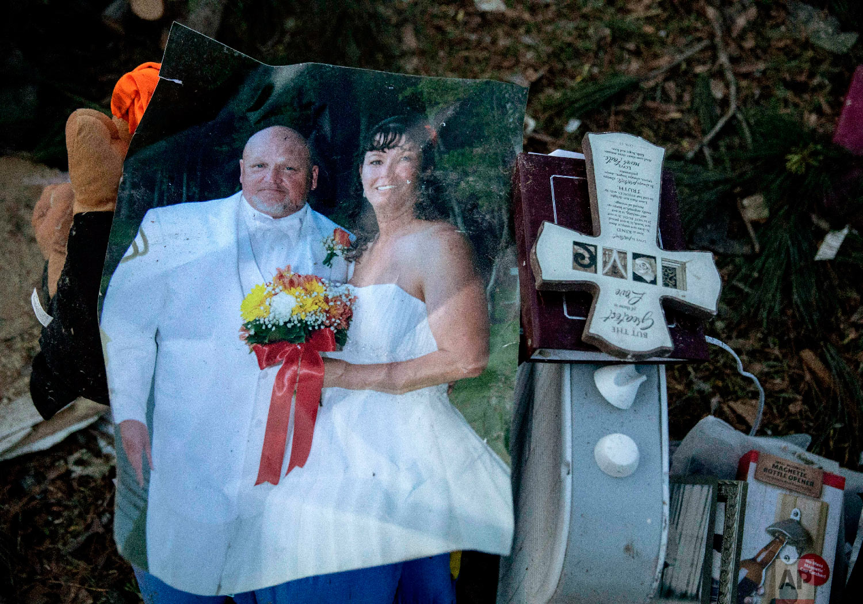 A wedding photo of Carol Dean and David Wayne Dean sits in a pile of personal items Carol Dean recovered in Beauregard, Ala., March 4, 2019. (AP Photo/David Goldman)