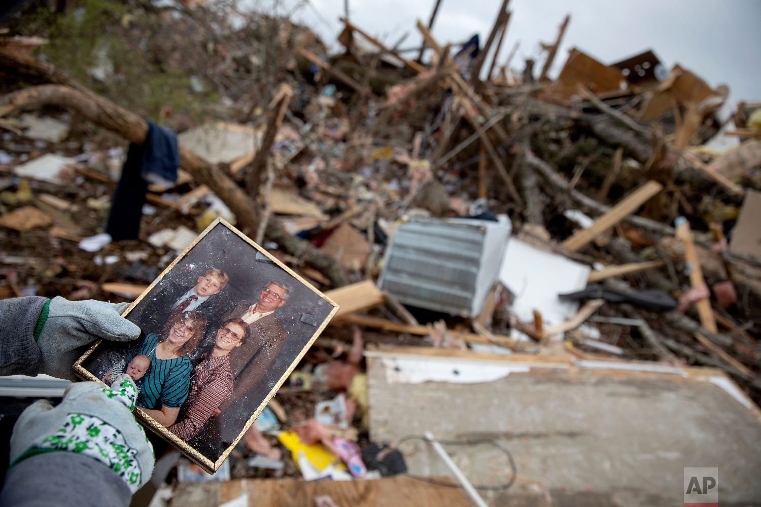 Danny Allen recovers a family photo while sifting through the debris of a friend's home destroyed in Beauregard, Ala., March 4, 2019. (AP Photo/David Goldman)