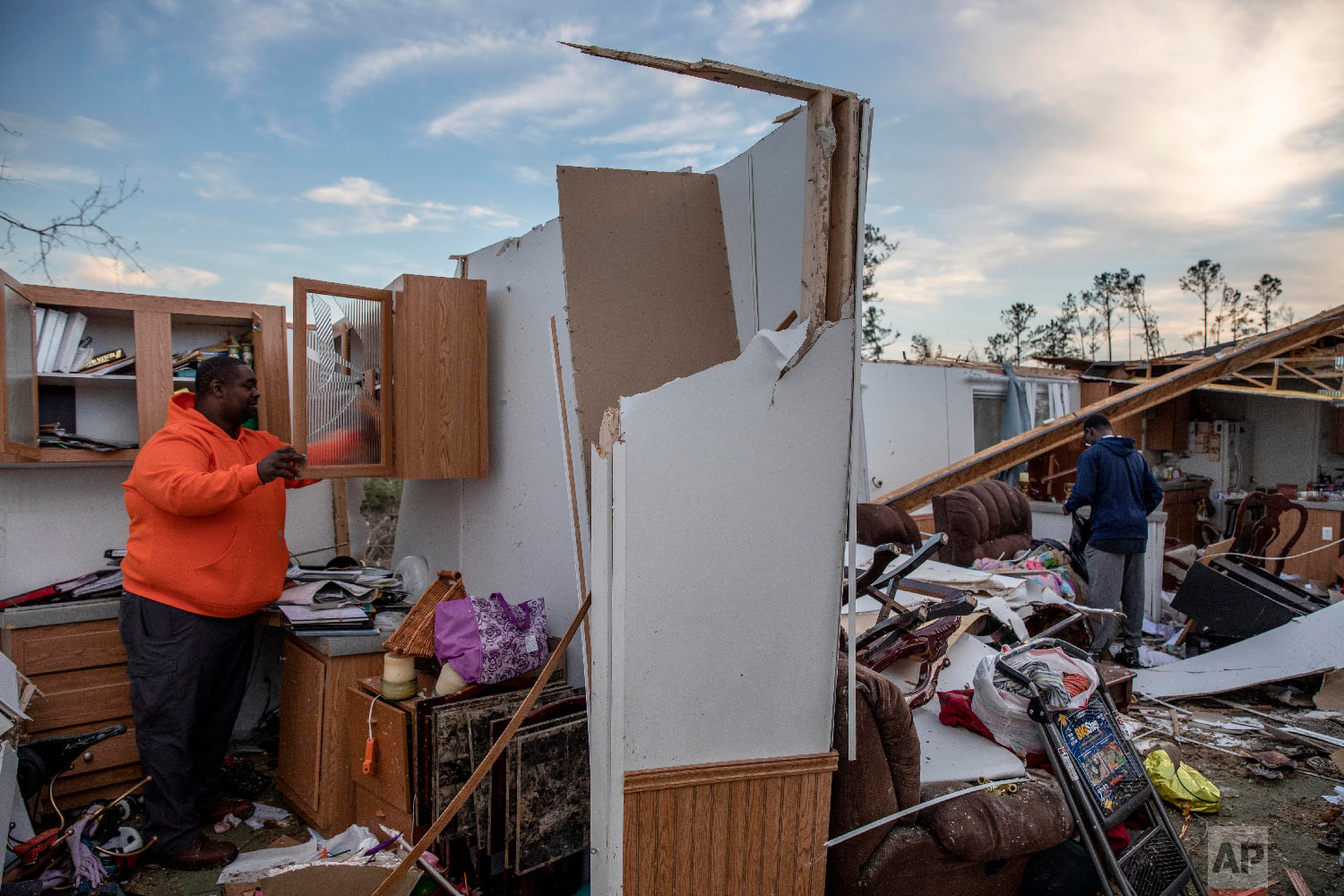 Granadas Baker, left, and son Granadas Jr. 18, right, retrieve personal items from the damaged home where they survived a tornado a day earlier in Beauregard, Ala., March 4, 2019. (AP Photo/David Goldman)