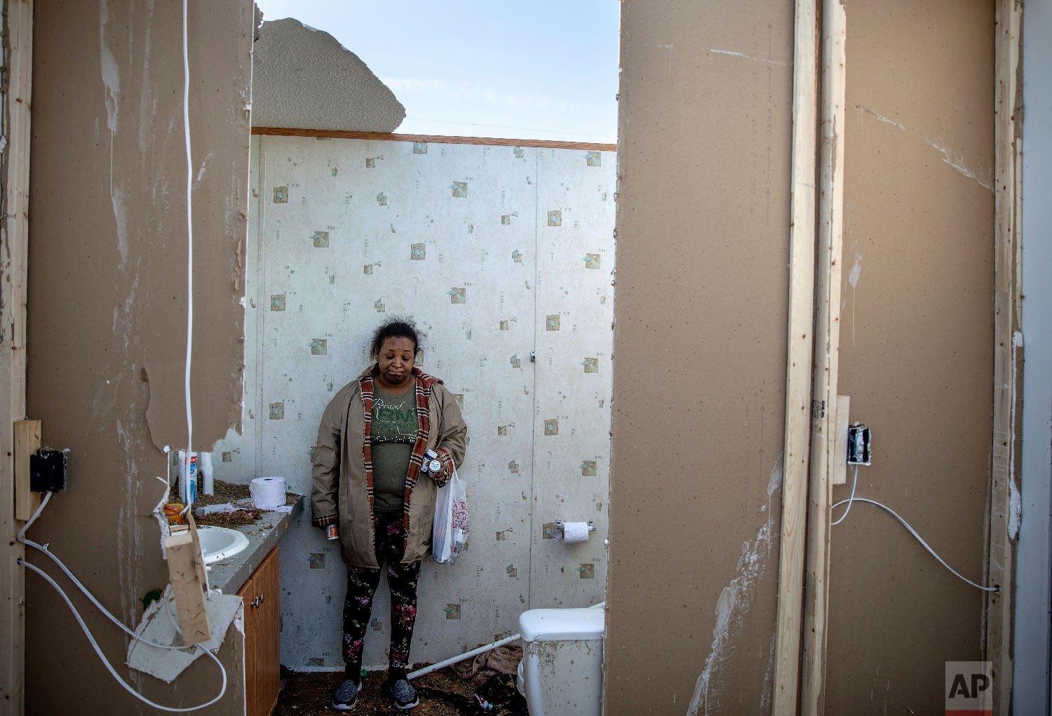 Shiraka Baker stands in the bathroom where she rode out a tornado with her husband and three children as she retrieves belongings from the damaged home in Beauregard, Ala., March 4, 2019. (AP Photo/David Goldman)