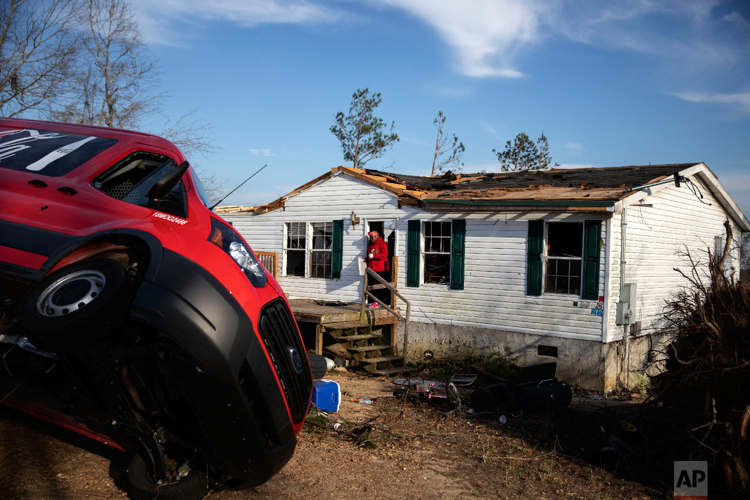 Kiara Slater carries out personal items from her parents' damaged home where they survived a tornado a day earlier in Beauregard, Ala., March 4, 2019. (AP Photo/David Goldman)