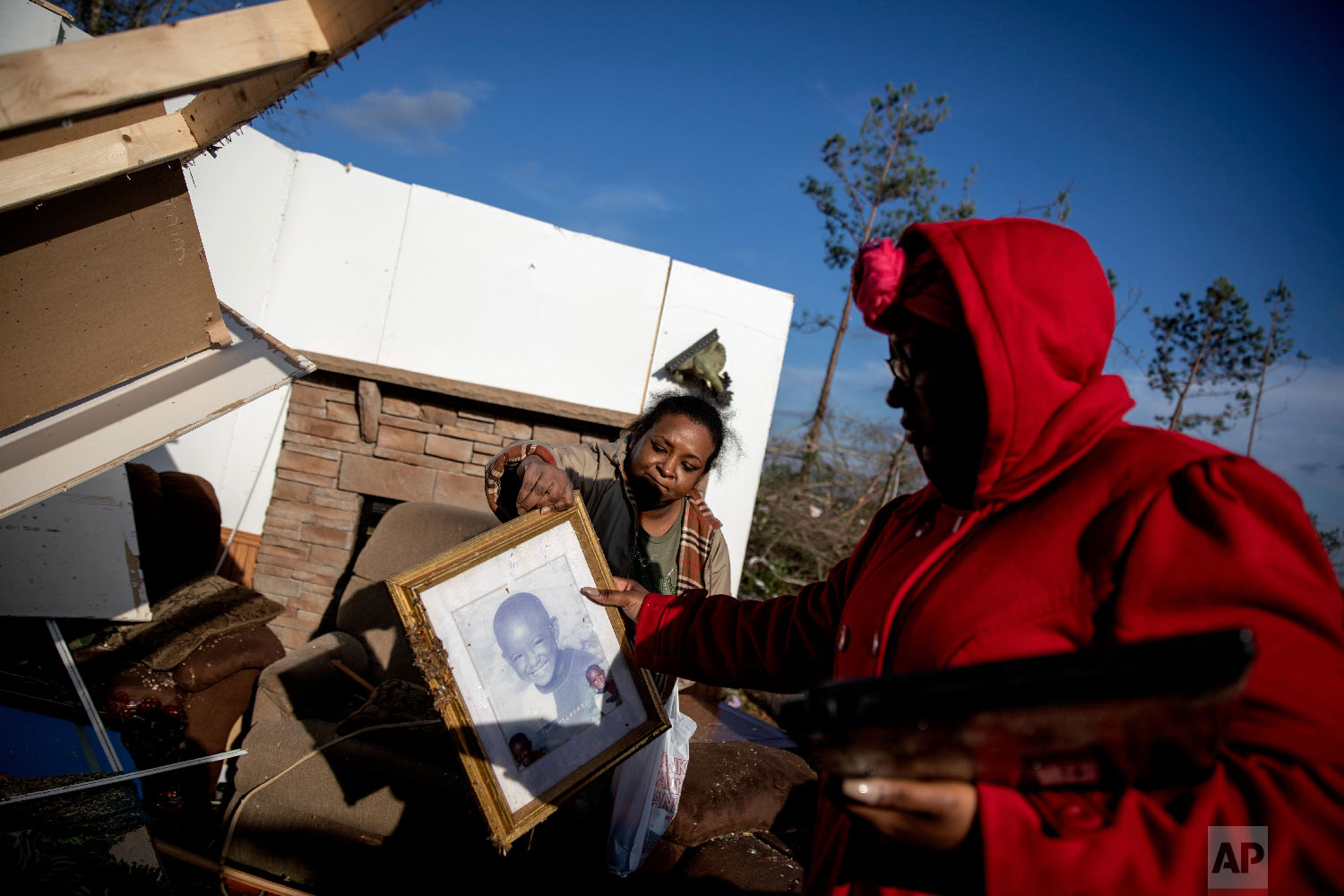 Shiraka Baker, left, passes a photo of her son to her daughter, Kiara Slater, while retrieving personal items from her damaged home where she survived a tornado a day earlier in Beauregard, Ala., March 4, 2019. (AP Photo/David Goldman)