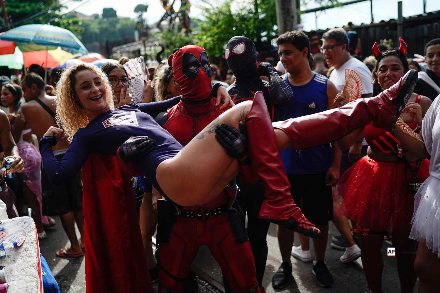 A reveler wearing a Deadpool costume carries a woman in a Super Woman costume as they enjoy the Carmelitas street party in Rio de Janeiro, Brazil, Friday, March 1, 2019. (AP Photo/Leo Correa)