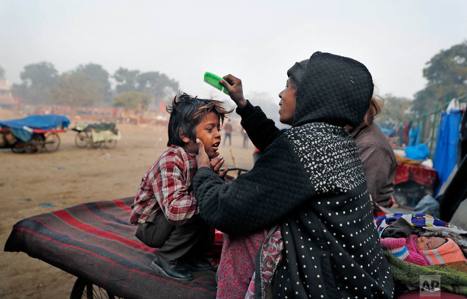 Ruby Khan helps her 7-year-old son Farmaan get ready for school in New Delhi, India on In this Jan. 18, 2019. (AP Photo/Altaf Qadri)