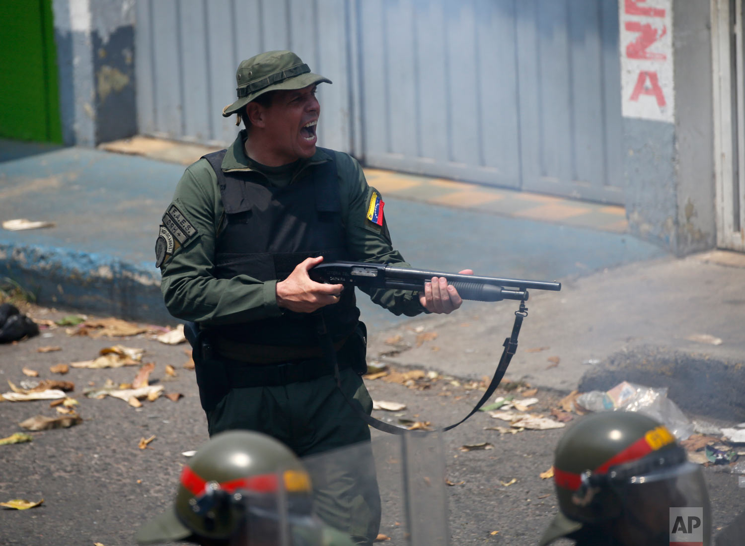 An officer of the Bolivarian National Guard fires his shotgun during clashes in Urena, Venezuela, near the border with Colombia, Feb. 23, 2019. (AP Photo/Fernando Llano)