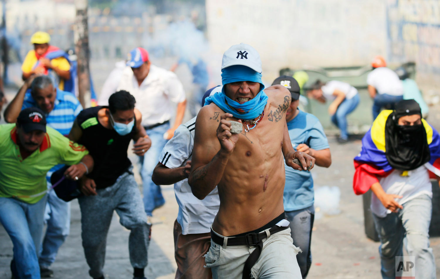 Demonstrators run from tear gas fired by Bolivarian National Guard officers during clashes in Urena, Venezuela, near the border with Colombia, Feb. 23, 2019.(AP Photo/Fernando Llano)