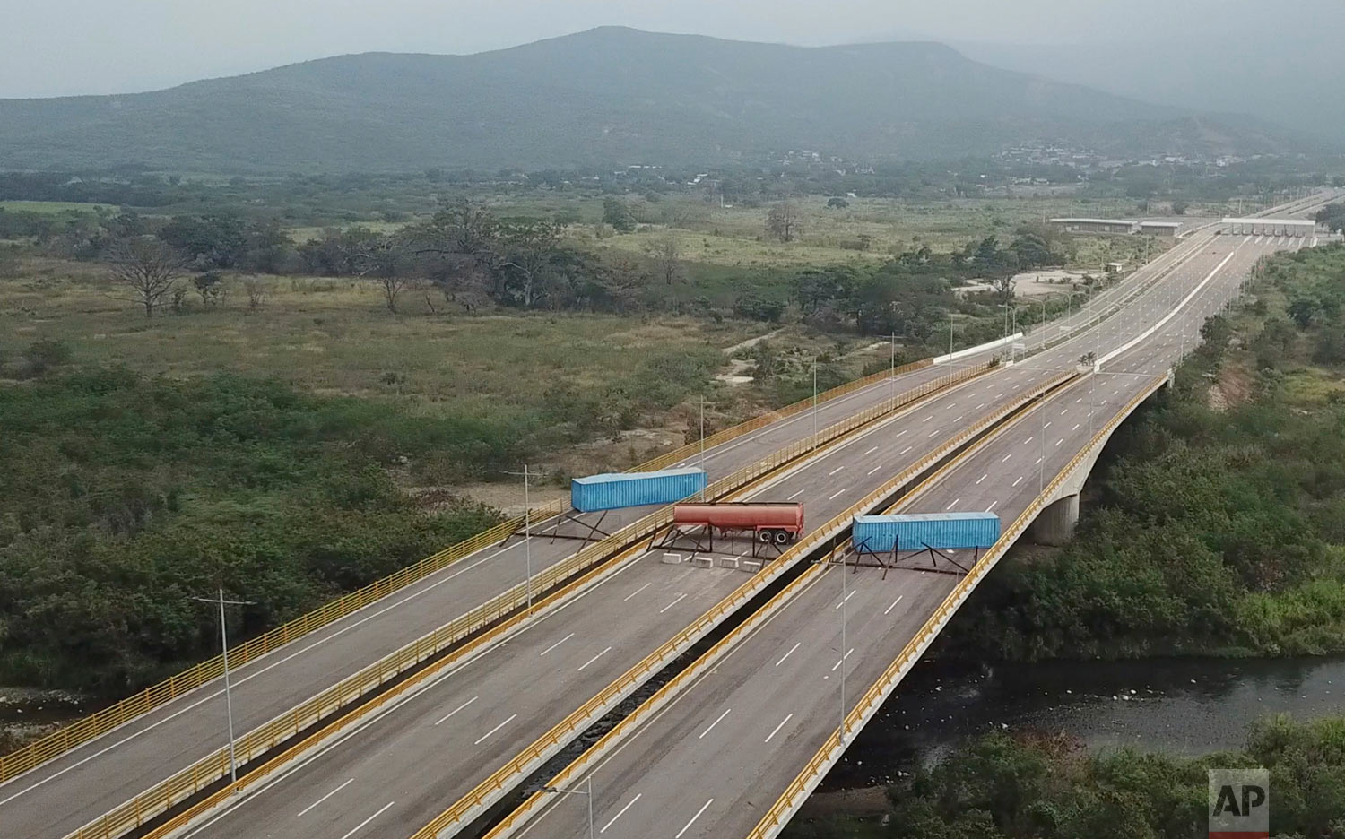 This image taken from video shows a fuel tanker, cargo trailers and makeshift fencing, blocking the Tienditas International Bridge in an attempt to stop U.S. humanitarian aid entering from Colombia into Venezuela, as seen from the outskirts of Cucuta, Colombia, Feb. 6, 2019. (AP Photo)