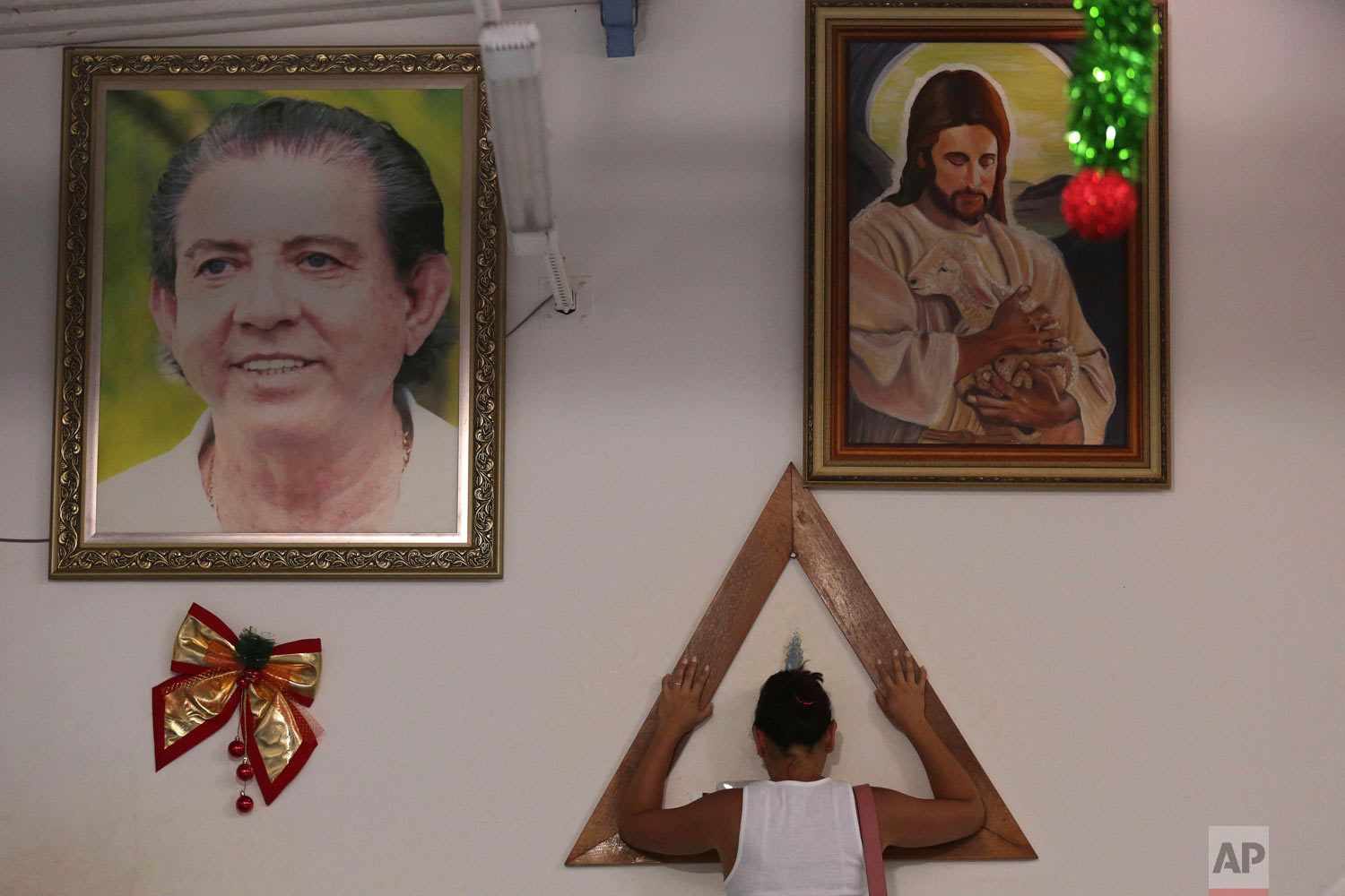 A woman places her hands in prayer on a wooden triangle, between framed images of spiritual healer Joao Teixeira de Faria and Jesus Christ, inside the Casa de Dom Inacio, in Abadiania, Brazil, Jan. 4, 2019. Hundreds of women have accused de Faria of sexual abuse. (AP Photo/Eraldo Peres)