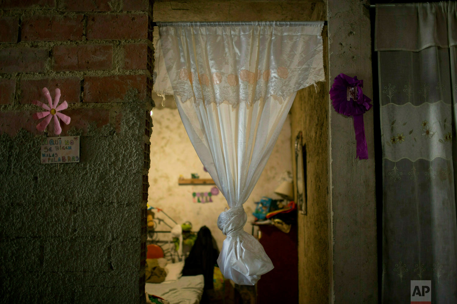 A curtain hangs in the bedroom doorway of slain Jhonny Godoy in La Vega slum of Caracas, Venezuela, Feb. 19, 2019. According to his family, two days after proclaiming his opposition to President Nicolas Maduro on Twitter, rifle-wielding special police agents wearing black masks stormed into their home, pulled him outside and shot the 29-year-old to death. (AP Photo/Ariana Cubillos)